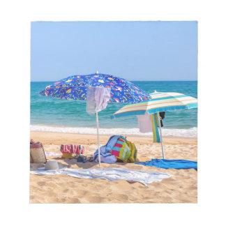 Two sun umbrellas and beach supplies at sea.JPG Notepad