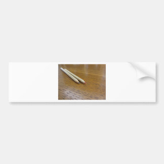 Two used colored pencils on wooden table bumper sticker
