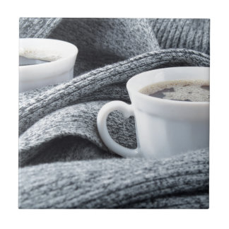 Two white cups of coffee wrapped in scarf tiles