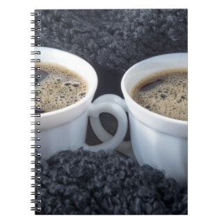 Two white cups with black coffee and foam notebook