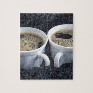Two white cups with black coffee and foam puzzle