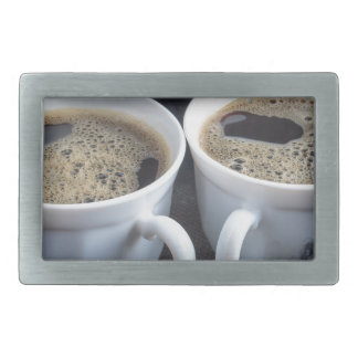 Two white cups with black coffee and foam rectangular belt buckles