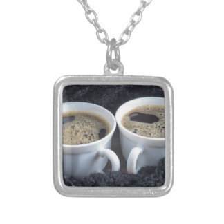 Two white cups with black coffee and foam silver plated necklace