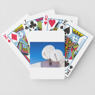 Two white satellite dishes on house wall bicycle playing cards