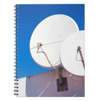 Two white satellite dishes on house wall notebooks