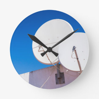 Two white satellite dishes on house wall round clock