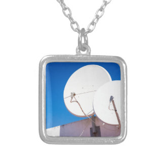 Two white satellite dishes on house wall silver plated necklace