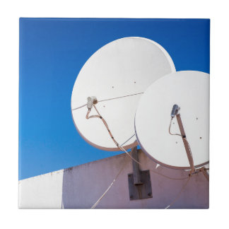 Two white satellite dishes on house wall tile