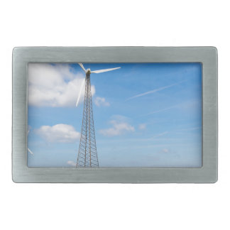 Two windmills in rural area with blue sky belt buckle