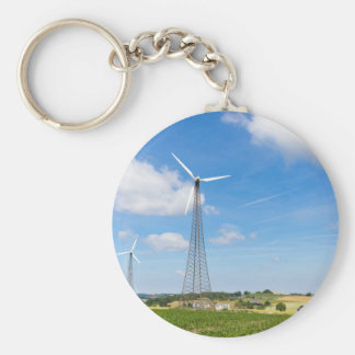 Two windmills in rural area with blue sky keychain