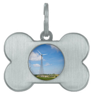 Two windmills in rural area with blue sky pet tag