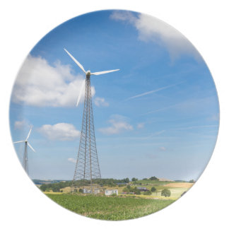 Two windmills in rural area with blue sky plate
