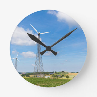 Two windmills in rural area with blue sky round clock