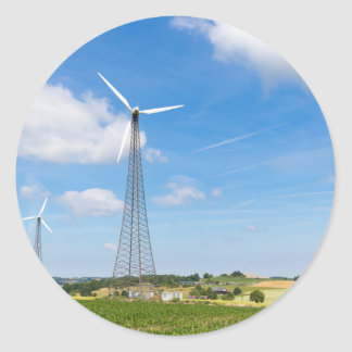 Two windmills in rural area with blue sky round sticker