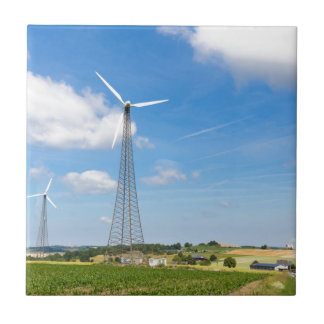 Two windmills in rural area with blue sky tile