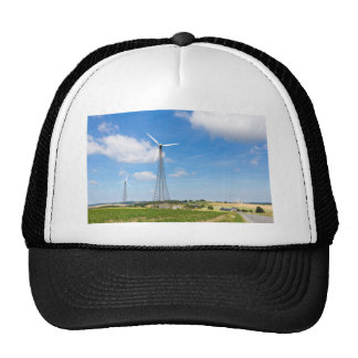 Two windmills in rural area with blue sky trucker hat