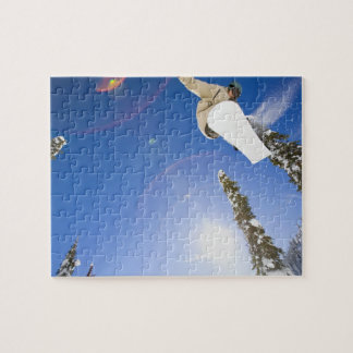 USA, Montana, Whitefish, Young man snowboarding Jigsaw Puzzle