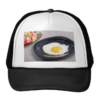 Useful homemade breakfast of fried egg and a salad trucker hat
