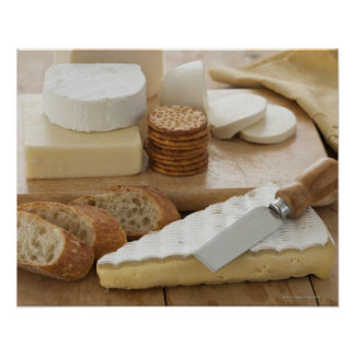 Various cheeses and bread on table poster
