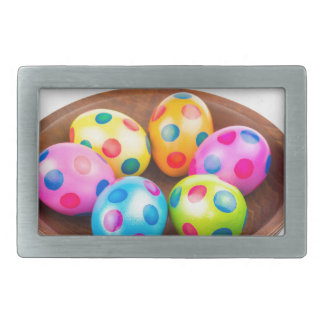 Various painted chicken easter eggs in wooden bowl belt buckle