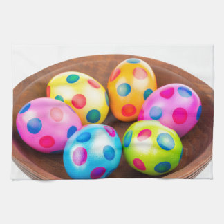 Various painted chicken easter eggs in wooden bowl kitchen towel