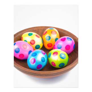 Various painted chicken easter eggs in wooden bowl letterhead