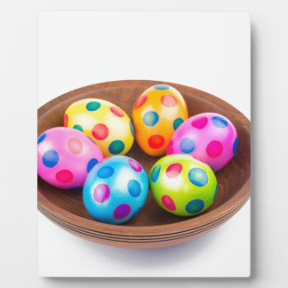 Various painted chicken easter eggs in wooden bowl plaque
