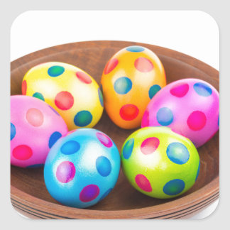 Various painted chicken easter eggs in wooden bowl square sticker