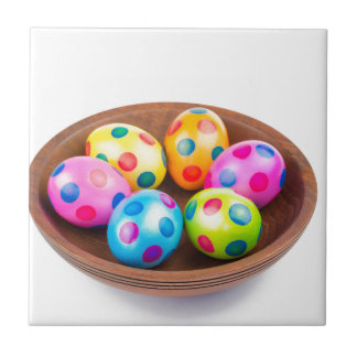 Various painted chicken easter eggs in wooden bowl tile