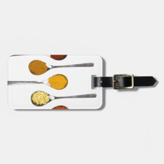 Various seasoning spices on metal spoons luggage tag