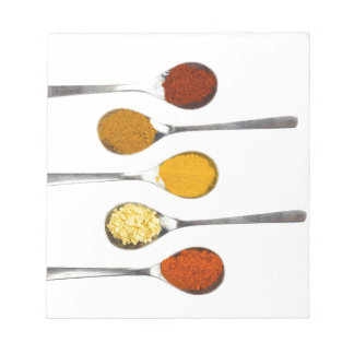 Various seasoning spices on metal spoons notepad