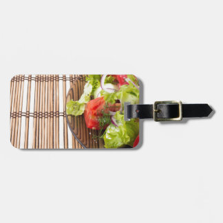 Vegetarian salad from fresh vegetables on a bamboo bag tag