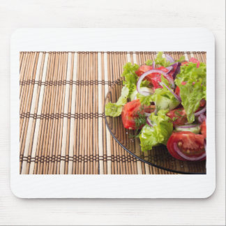 Vegetarian salad from fresh vegetables on a bamboo mouse pad
