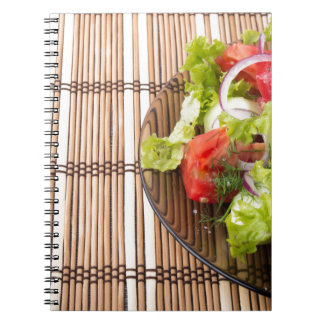 Vegetarian salad from fresh vegetables on a bamboo notebooks