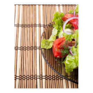 Vegetarian salad from fresh vegetables on a bamboo postcard