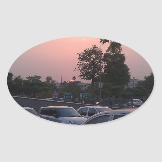 Vehicles in a parking lot at sunset oval sticker