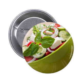 Vertical view close-up on a green bowl with salad 2 inch round button