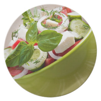 Vertical view close-up on a green bowl with salad party plates