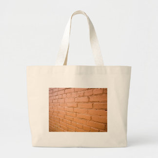 View angle on the red brick wall large tote bag