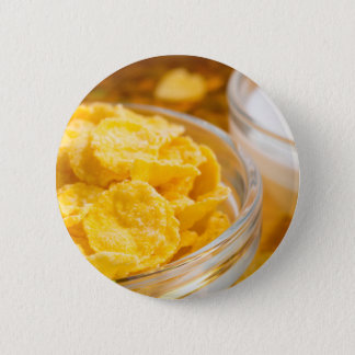 View close-up of milk and a glass bowl of flakes 2 inch round button