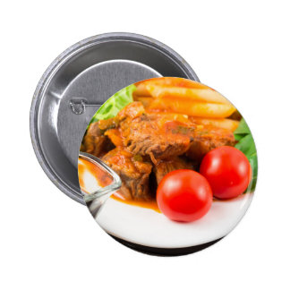View close-up on a meal of beef stew with pasta 2 inch round button