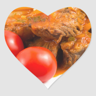 View close-up on a meal of beef stew with pasta heart sticker
