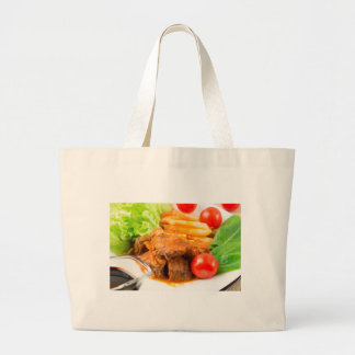 View close-up on a meal of beef stew with pasta large tote bag