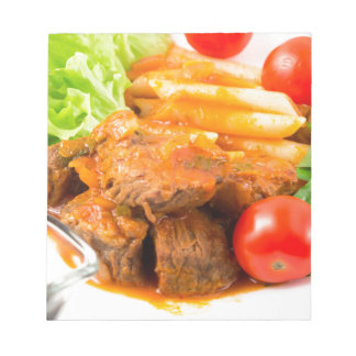 View close-up on a meal of beef stew with pasta notepad