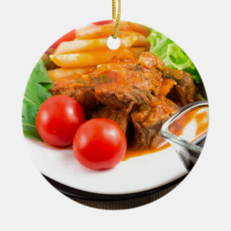 View close-up on a meal of beef stew with pasta round ceramic ornament