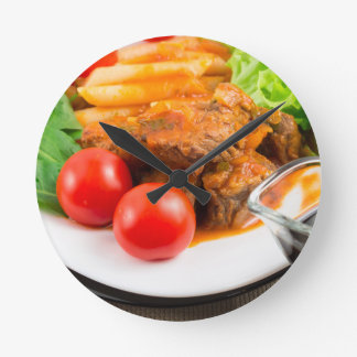View close-up on a meal of beef stew with pasta round clock