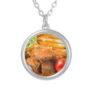View close-up on a meal of beef stew with pasta silver plated necklace