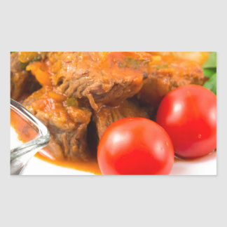 View close-up on a meal of beef stew with pasta sticker