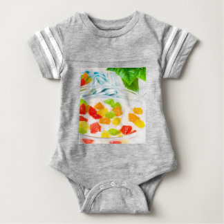 View close-up on oatmeal with colorful candied baby bodysuit