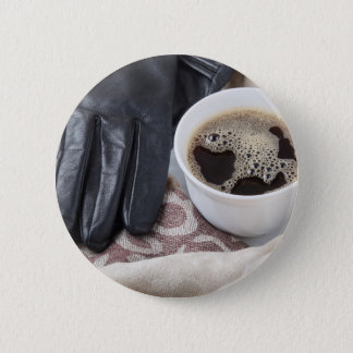 View close-up on white cup of coffee and gloves 2 inch round button